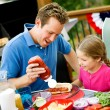 Summer: Dad Helps Girl with Hot Dog — Stock Photo
