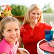Summer: Girl at Table with Mother Behind — Stock Photo