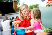 Summer: Mom Gets Hot Dog for Girl — Stock Photo
