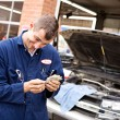 Stock Photo: Mechanic: Couting Money From Scamming Customer