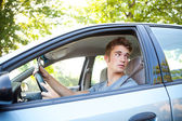 Driving: Driver Turning and Holding Cell Phone — Stock Photo