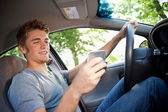 Driving: Paying Attention to Phone Instead of Driving — Stock Photo