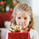 Christmas: Little Girl Holds Christmas Present — Stock Photo