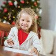 Stock Photo: Christmas: Little Girl Writing Letter To Santa Claus