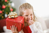 Christmas: Young Girl Holds Christmas Present To Ear — Stock Photo