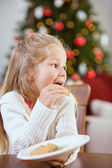 Christmas: Sneaky Girl Eats Christmas Cookies — Stock Photo