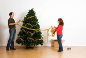 Christmas: Putting Tinsel or Garland on Tree — Stock Photo