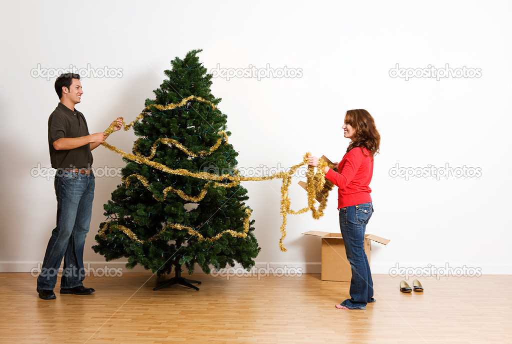 Christmas putting tinsel or garland on tree stock photo How to decorate a christmas tree without tinsel