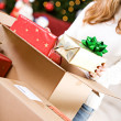 Christmas: Putting Wrapped Gifts In Box — Stock Photo #33802147