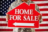 Soldier: Holding a Home for Sale Sign — Stock Photo