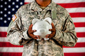 Soldier: Holding a Piggy Bank — Stock Photo