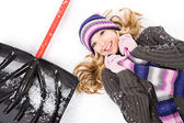 Winter: Pretty Woman Lying Next to Snow Shovel — Stock Photo