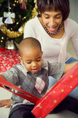 Family: Cute Boy Unwrapping Christmas Gift — Stock Photo