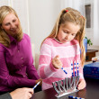 Stock Photo: Hanukkah: Girl Puts Candles in Menorah