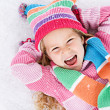 Winter: Laughing Little Girl Lying In Snow — Stock Photo #36650885
