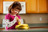 Kitchen Girl: Ready to Eat a Banana — Stock Photo