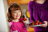 Kitchen Girl: Taking a Berry from a Plate — Stock Photo