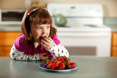 Kitchen Girl: Tasting Strawberries — Stock Photo