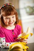 Kitchen Girl: Eating a Banana — Stock Photo
