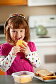 Kitchen Girl: Eating a Slice of Cheese — Stock Photo