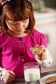 Kitchen Girl: Dunking Cookie in Milk — Stock Photo
