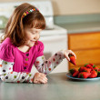Kitchen Girl: Taking a Strawberry — Stock Photo