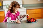 Kitchen Girl: Taking a Strawberry — Stock Photo