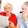 Seniors: Couple Shocked By Something In Newspaper — Lizenzfreies Foto