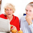 Stock Photo: Seniors: Couple Shocked By Something In Newspaper