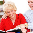 Stock Photo: Seniors: Couple Looking At Old Scrapbooks