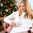 Christmas: Smiling Woman Cutting Wrapping Paper — Stockfoto