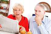 Seniors: Couple Shocked By Something In Newspaper — Stock Photo