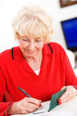 Seniors: Woman Cheerfully Writing Checks — Stock Photo