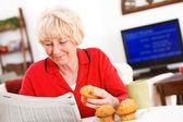 Seniors: Woman Reading Paper At Breakfast — Stock Photo