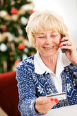 Christmas: Woman Using Credit Card Over Phone — Stock Photo