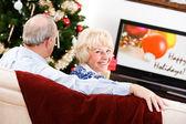 Рождество: пара сидеть и смотреть праздник телевидения — Стоковое фото