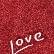 Foto Stock: Glitter: Love Written in Red Glitter Background