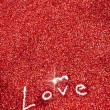图库照片: Glitter: Love Written in Red Glitter Background