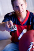 Football: Guy Holds Remote Control And Watches Team On TV — Foto Stock
