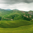 Panoramic view of green meadows and mountains — Stock Photo