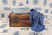 Suitcase, maps and neckerchief are on the sofa. — Stock Photo