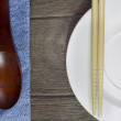 Wood background plates, chopsticks and spoons on blue jeans text — Stock Photo