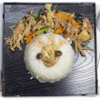 Mushrooms stir fry with rice on black plate — Stock Photo