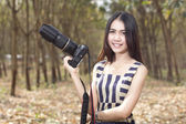 Fashion of a autumn girl wearing a striped holding the camer — Stock Photo