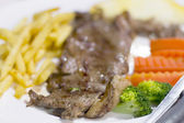 Grilled steak with french fries soft focus — Stock Photo