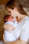 Happy mother kissing her baby infant — Stock Photo