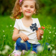 Smiling girl on the meadow with flowers — Stock Photo