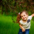 Happy child playing in a spring garden — Stock Photo