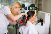 Woman at the hairdresser blow drying her hair — Stock Photo