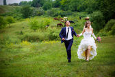 Bride and groom walk in the park — Stock Photo